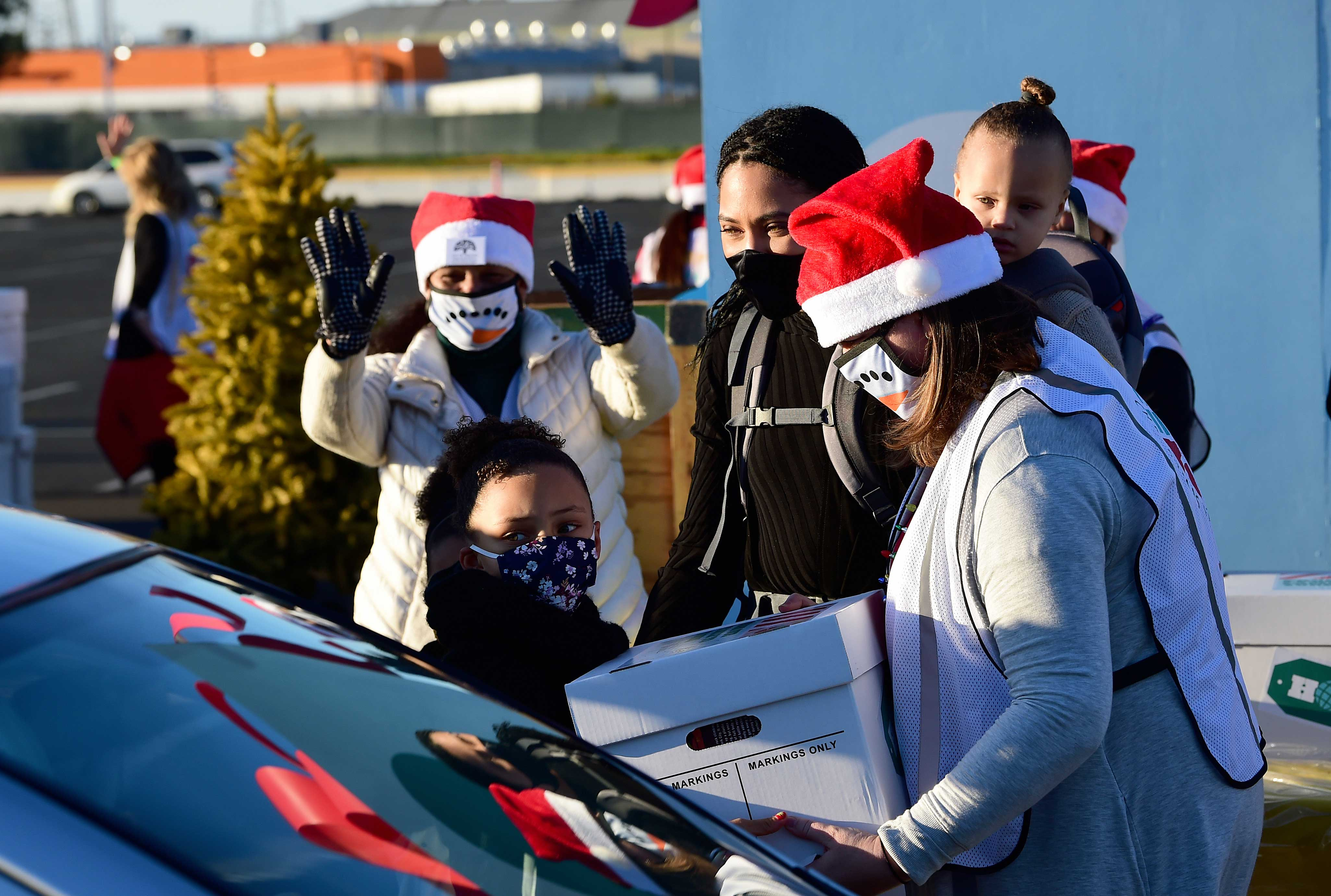"""Ayesha Curry and family distributing resources at """"8th Annual Christmas with the Curry's"""" holiday surprise at Oakland Arena. Photo courtesy of Eat. Learn. Play."""